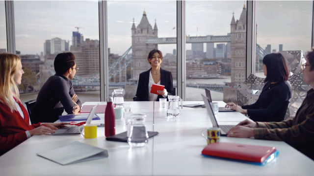 A woman is in a meeting with four other people, Tower bridge is in the background.
