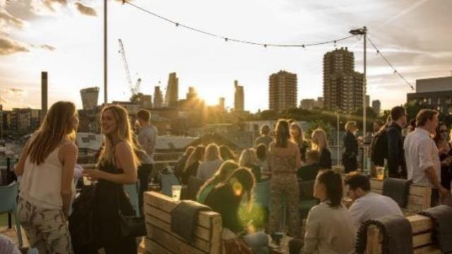 Groups of young people having a drink on a rooftop bar overlooking the London skyline at sunset.