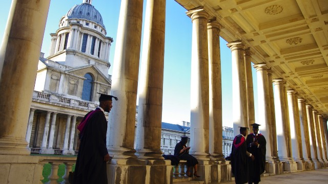 Four students in their graduation robes are standing outside a beautifully arched building.