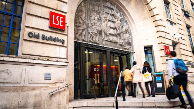 Students with bags and backpacks enter LSE via the Old Building entrance.