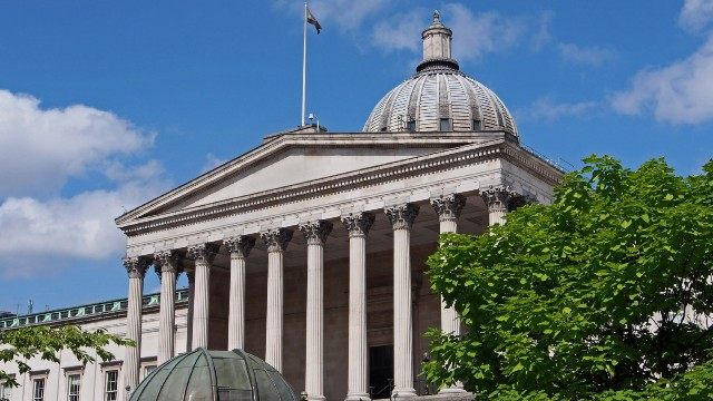 The columned entrance of UCL in London on a bright and sunny day.