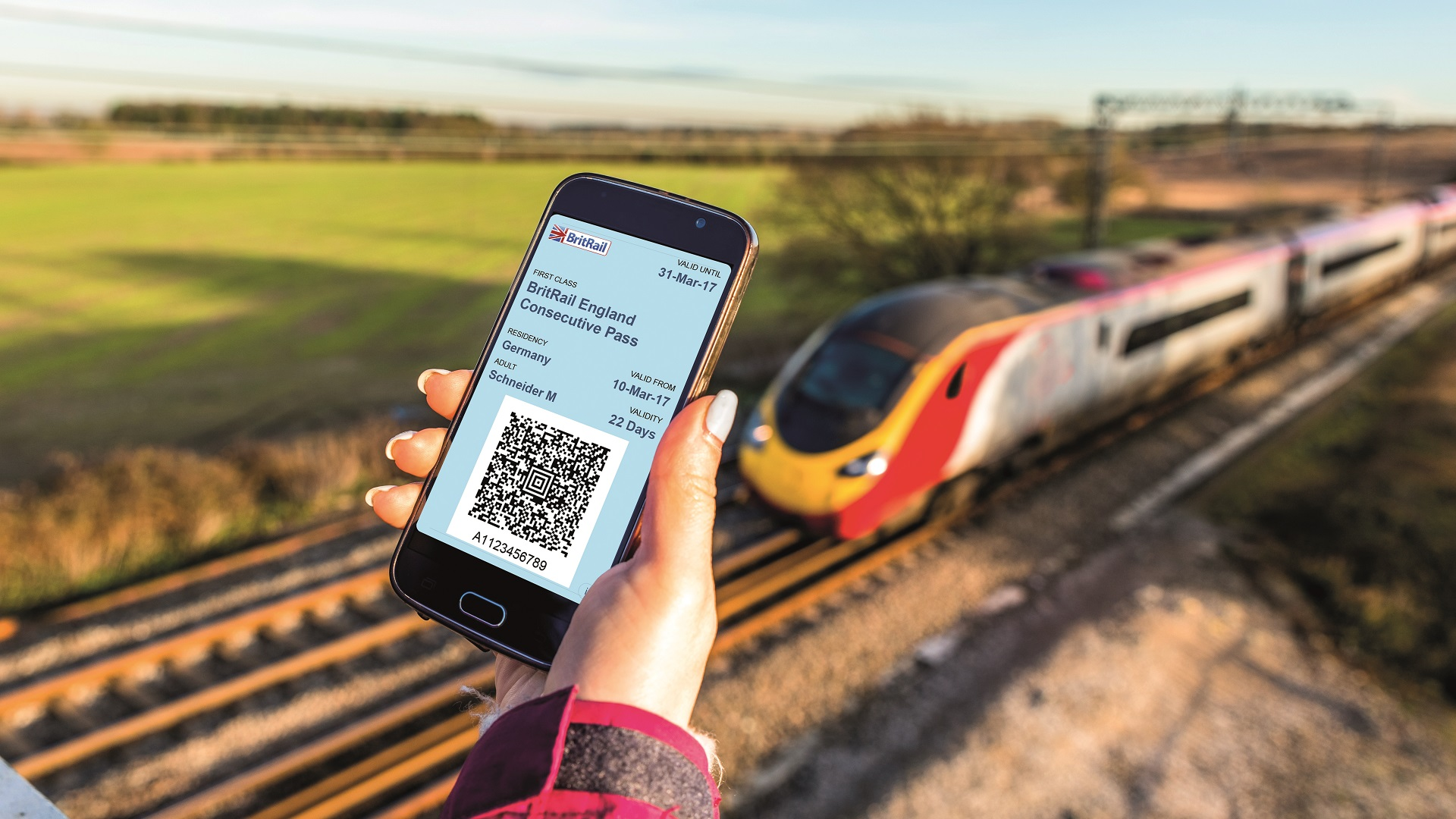 hand holds phone with BritRail app in front of a train passing through English countryside