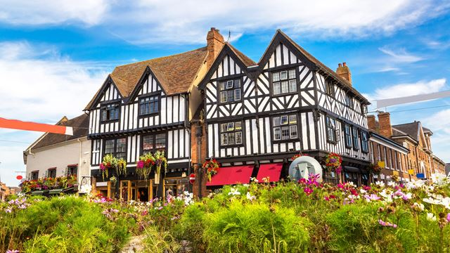 Flowers outside Tudor buildings with a blue sky overhead in Stratford-upon-Avon