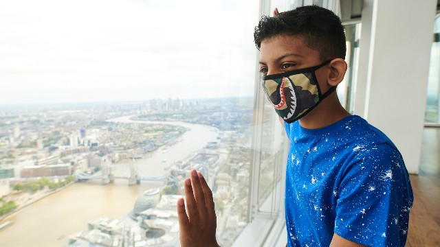 A young boy wearing a face covering looks out over the London skyline from The View from The Shard.