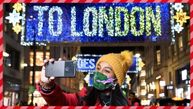 """A lady wearing a face covering and a yellow bobble hat takes a selfie of the blue and yellow Oxford Street lights, which read """"TO LONDON""""."""
