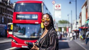 A smiling girl waits for a bus at a bus stop on sunny summer's day in London.