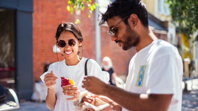 A man and a woman wearing sunglasses smile while tucking into takeaway food in the sunshine as they explore Brixton.