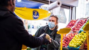 A woman wearing a mask hands over a melon to a customer at a fruit stall in a market.