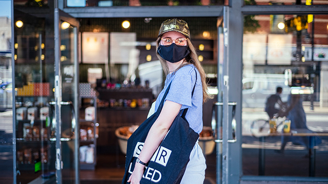 A woman, wearing a face covering and carrying a bag, waits to go inside a shop.