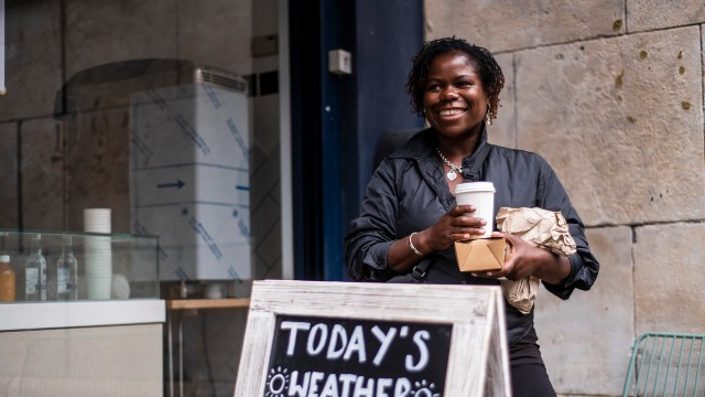A smiling woman stands outside a cafe holding her takeaway order.
