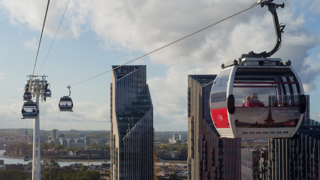 The Emirates Air Line cable cars flying above London's skyscrapers and the river Thames.