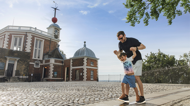 The sun shines as a man and child walk over the Prime Meridian Line outside the Royal Observatory Greenwich.