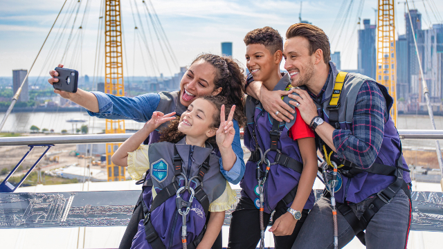 A smiling family is taking a selfie with the city in the background on top the Up at the O2.