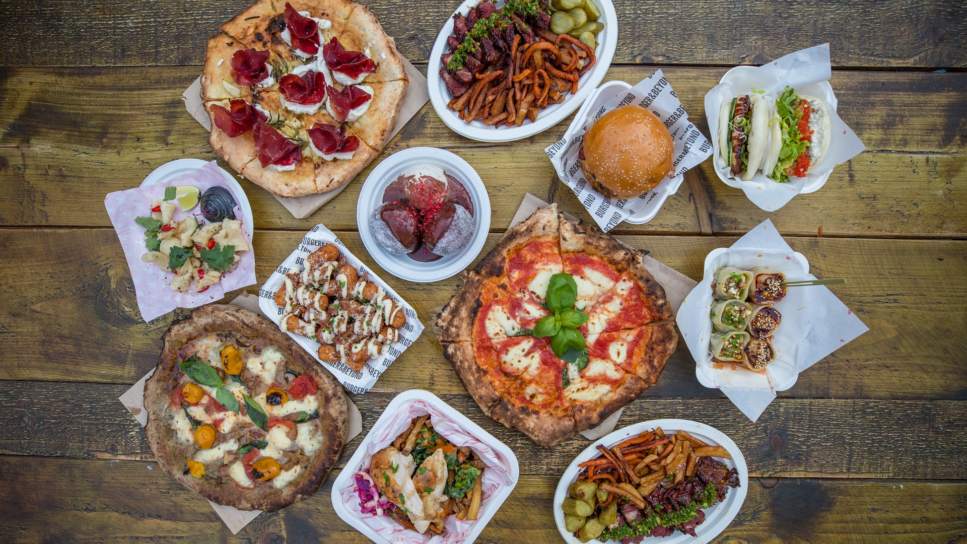 An array of street food staples on a wooden table including pizza and burgers.