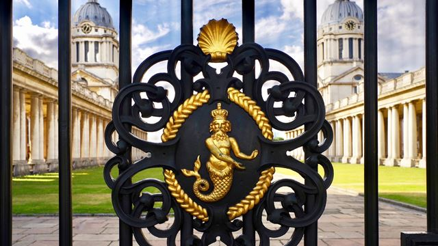 Close up of Old Royal Naval College's gate with gold mermaid detail.