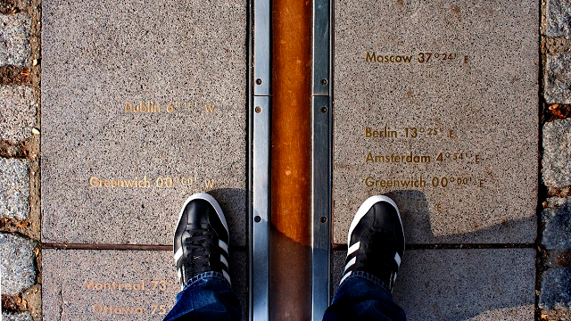 The Prime Meridian Line viewed from a visitor's perspective with feet in the shot.