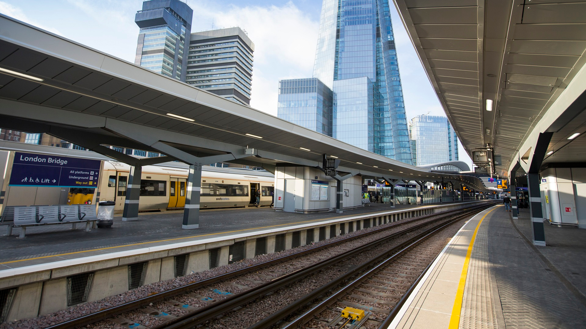London Bridge station platform with train and tall buildings in the background.