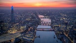 The sun sets over the river Thames as its bridges glow with colourful lighting as part of the Illuminated River installation