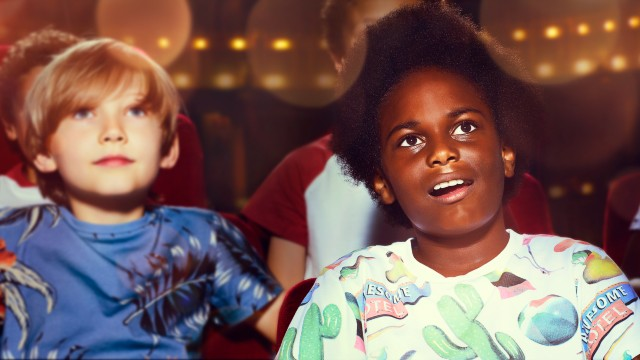 Children sit in the audience and enjoy a show at a theatre during Kids Week