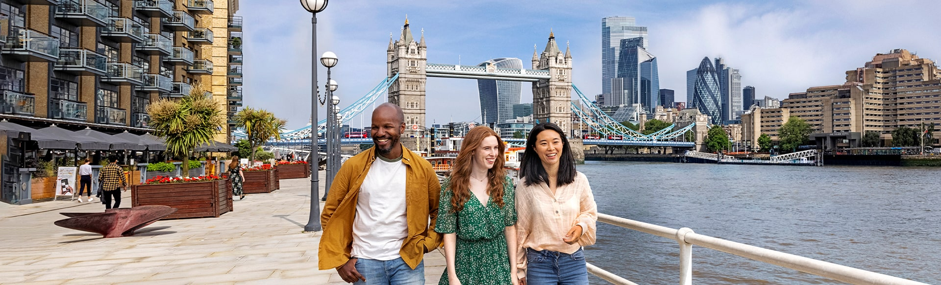 Man and two women walking alongside the river Thames with Tower Bridge and the City of London in the background