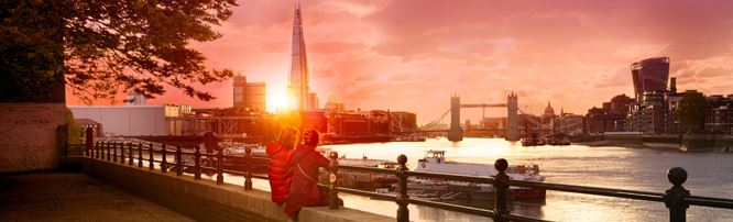 Two people sit on the banks of the river Thames to watch the sun set over the London skyline including The Shard and Tower Bridge.