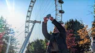A woman takes a photo on her smartphone, with the London Eye in the background.