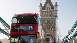 A red double-decker London bus goes across Tower Bridge.