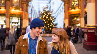 A young couple look into each others' eyes at Leadenhall Market, with a Christmas tree in the background