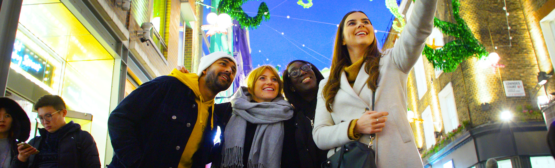 A group of four young adults takes a selfie in front of the Christmas lights on Carnaby Street, with green seahorse decorations suspended between buildings.