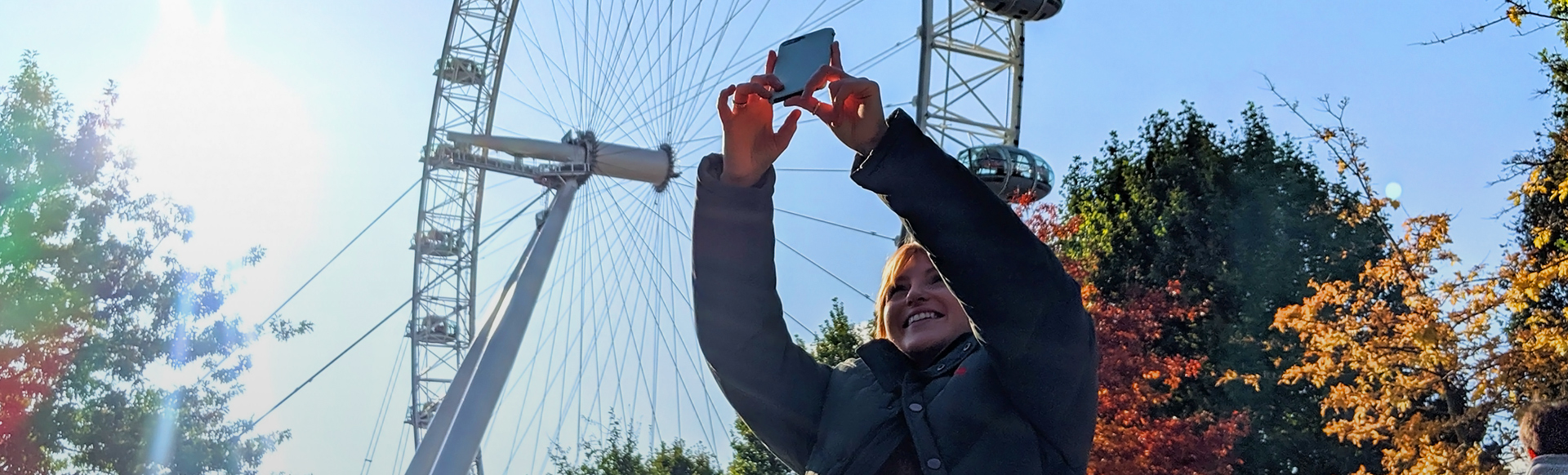 A woman takes a photo with her smartphone, with the London Eye in the background.