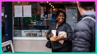 "A lady stands in front of a shopfront with a takeaway coffee cup and food wrapped in a brown paper bag, she's smiling as a man walks past in the foreground. A logo worded ""Because I'm a Londoner"" is overlaid on the image, inside a speech bubble."