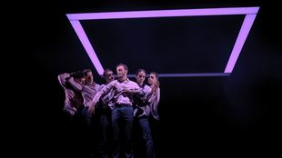 Six members of BalletBoyz gather in a dark space beneath a neon purple square light on stage.