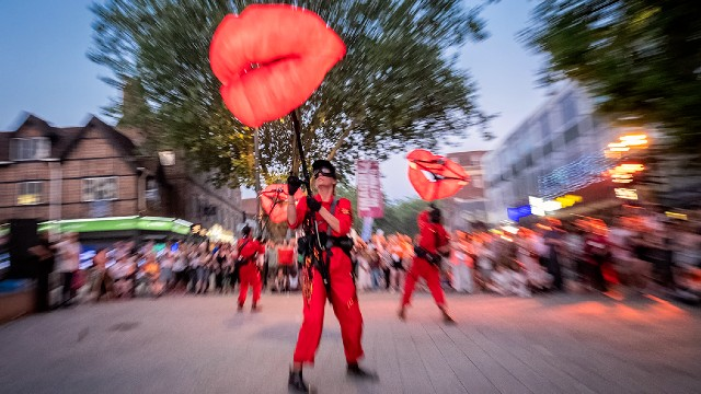 Performers dressed in red holding big red lip-shaped puppets in front of a crowd.