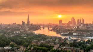 Sunset over London with orange sky and cityscape on horizon with river Thames running through the middle