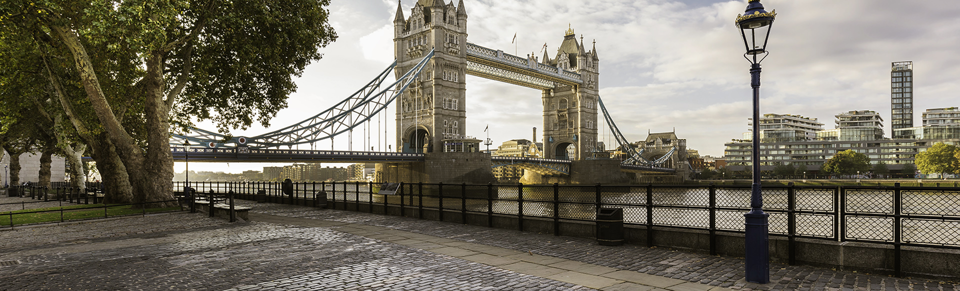A cobbled riverside pathway in the foreground with Tower Bridge and the river Thames in the background.