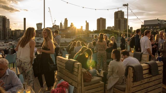 People are socialising in a rooftop bar on a warm summer evening
