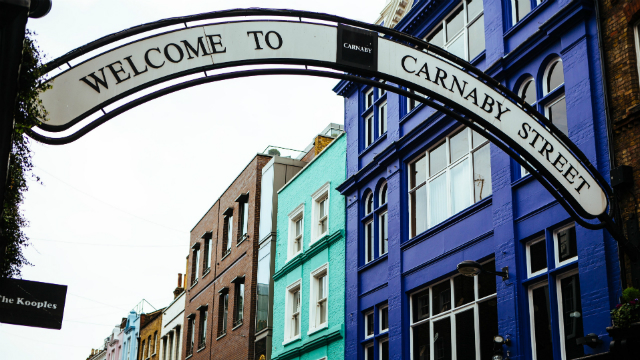 The famous Carnaby Street arched street sign stretching over the entrance to the street with blue painted buildings in background