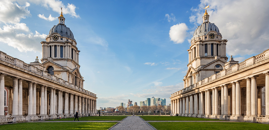 Cityscape of London on horizon through the middle of the Old Royal Naval College in Greenwich.