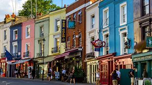 Colourful painted shop fronts on a street in Notting Hill, London.