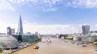 Sun shines over the Thames and London landmarks including City Hall, The Shard and the Walkie Talkie.