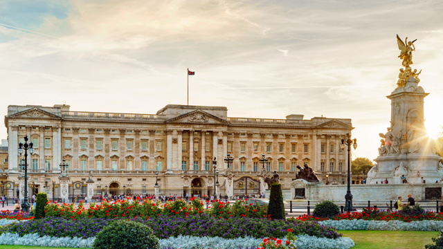 The sun sets behind Buckingham Palace which is lit with a golden glow