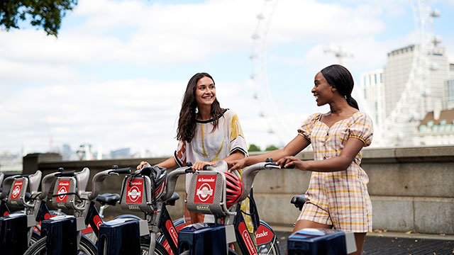 Two ladies in short-sleeved clothing smile at each other while holding a Santander Cycles bicycle each, with the London Eye in the background.