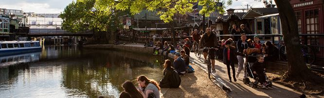 Camden Lock and Regent's Canal, with visitors sitting and walking next to the canal. © London and Partners/Michael Heffernan