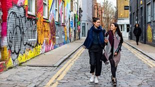 Couple smile at each other as they walk down road past Shoreditch street art on a date.