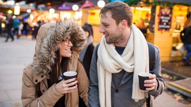 Deux jeunes gens se baladent l'un à côté de l'autre,  une boisson chaude à la main.
