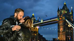 A couple kissing at dusk with Tower Bridge in the background.