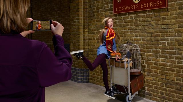 A young woman with long hair is posing pushing a Harry Potter trolley, half way trough a wall.
