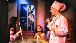 Two children and a live actor mixing a big pot at the Shrek's Adventure! London.