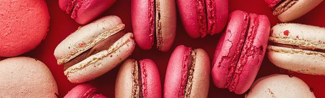 A selection of pink macarons with chocolate filling.