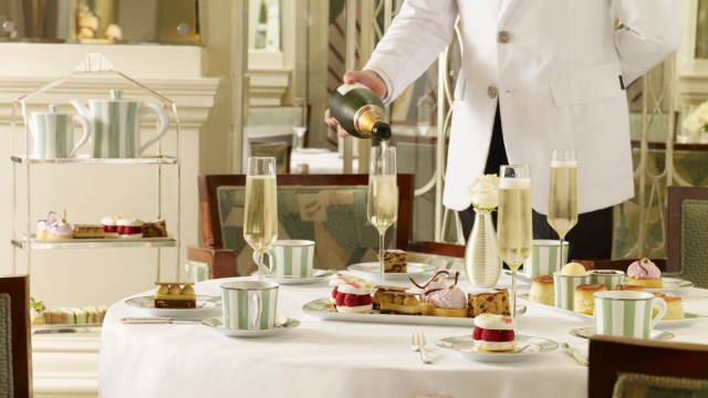 Waiter pouring champagne into flutes accompanying afternoon tea scones and sandwiches.